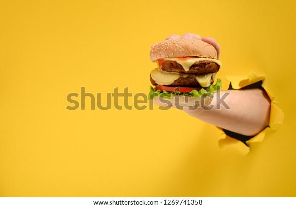 Hand nimmt einen großen Burger durch zerrissenen gelben Papierhintergrund mit Kopienraum. Kann einem leckeren Fastfood-Gericht nicht widerstehen.