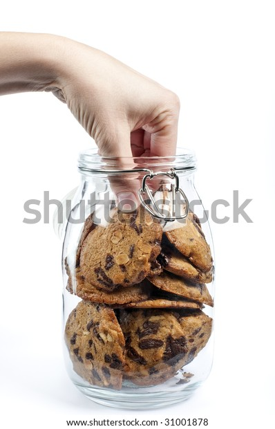 A hand taking cookies from a glass jar on white background
