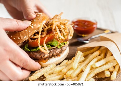 Hand taking hamburger from wooden tray. Side view on man holding burger with onions for eating. American cuisine, lunch time, snack, fast junk food concept
