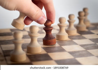 Hand taking his next step on chess game. Human hand moving dark chess pawn piece on Chess board.
