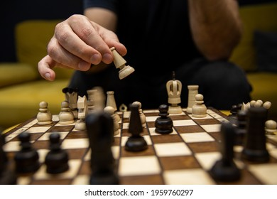 Hand taking his next step on chess game. Human hand moving wooden dark chess bishop piece on Chess board. Chess pieces in style of minimalist abstract design
