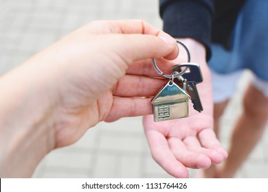 Hand taking house key from realtor hand closeup view on blurred background. Real estate agent giving keys to apartment owner. Buying selling or renting house or apartment property business concept.