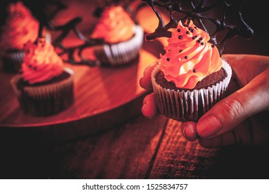 hand taking one of Halloween cupcakes with buttercream and chocolate spiderwebs in the mist. Dark, rustic, wooden background