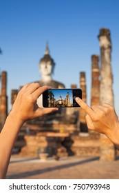 A hand taking photo of Buddha statue with smartphone, Sukhothai, Thailand
