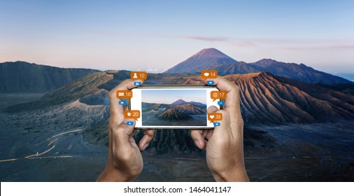 Hand taking photo of Mount Bromo volcanic, famous travel destination in Indonesia with social media notification icons