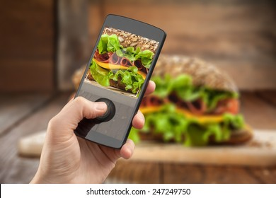 Hand taking photo of sandwich with smatphone on the wooden table with slices of tomatoes, ham, cheese and lettuce