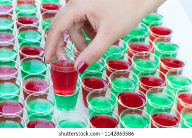 a Hand is taking a red jelly shot