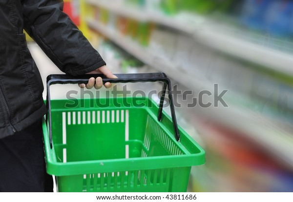 hand is taking the shopping basket in the market