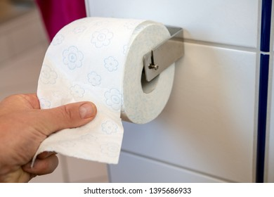 hand taking white toilet paper on wall with white tiles