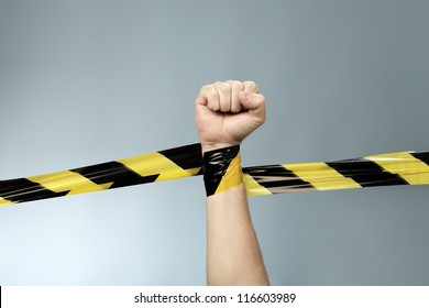 Hand tangled in black and yellow barrier tape.