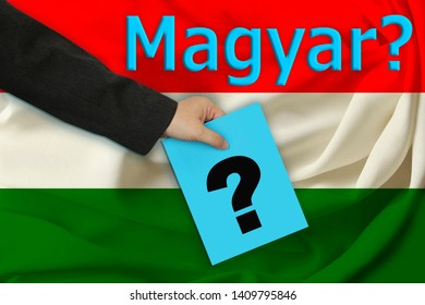"hand of the teacher holds a question mark on the background of the inscription in the Hungarian ""Hungarian language?"" and a beautiful flag of hungary on pleated fabric"