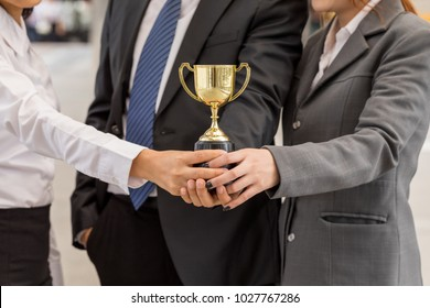 hand of Team business happy expression holding a golden trophy our success. Make winner gesture. Concept Teamwork is the best for business