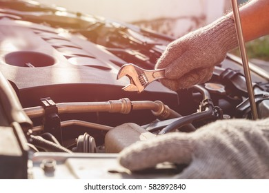 Hand of technician checking or fixing engine of modern car.