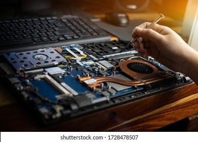Hand technician repairing broken laptop notebook computer with a screwdriver