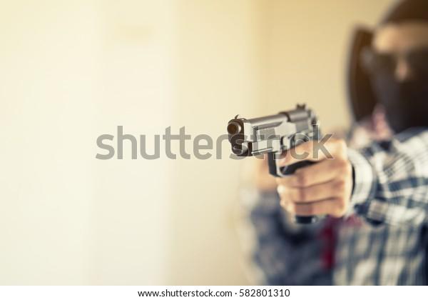 Hand of terrorist holding a gun