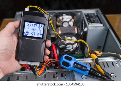 Hand tester of power supply unit. Open computer case. Professional diagnostic device. Digital measuring tool, connectors, colorful cables, pliers and screwdriver. PC hardware maintenance. Technician.