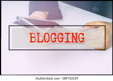 Hand and text BLOGGING with vintage background. Technology concept.