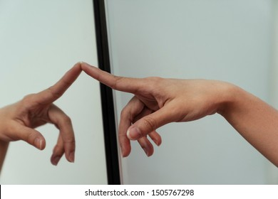 The hand of Thai woman that pointing to the mirror.