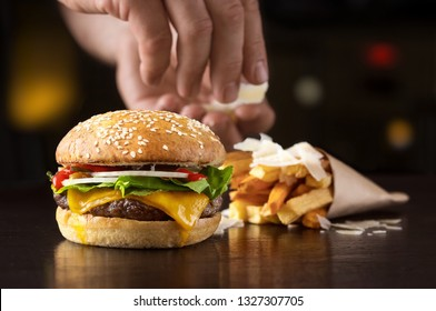 Hand that arranges beef burger with fried potatoes and cheese