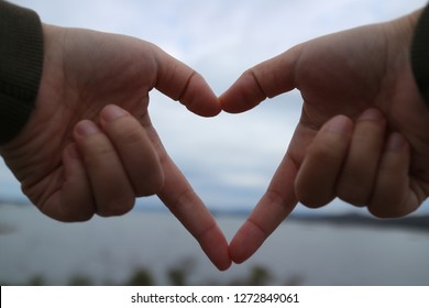 The hand that is in harmony with love is the heart, the sky background.