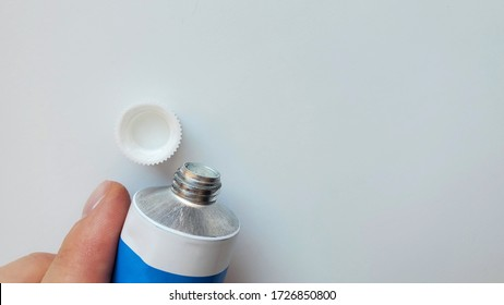 hand that holds a tube with cream on a white backgroun