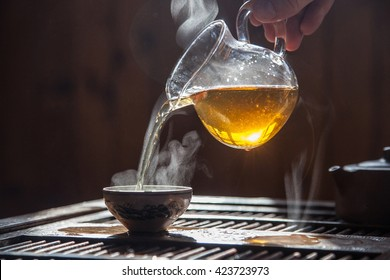 Hand that pours chinese green tea from glass kettle to smal cup