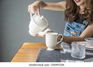 Hand that pours chinese green tea from glass kettle to  cup