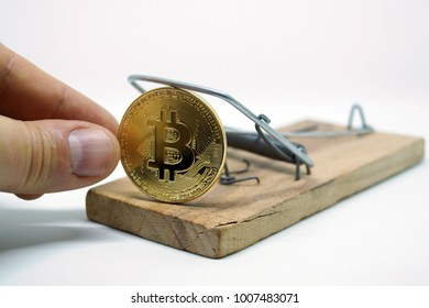 A hand that takes a coin of bitcoin from mousetrap. Risks and dangers of investing in the crypto currency.