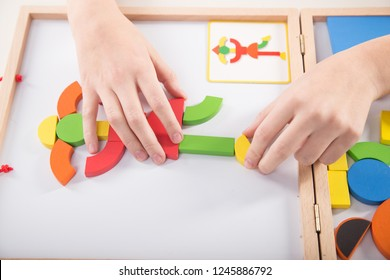 Hand therapy. Child playing with magnetic blocks for motor therapy. Educational games.