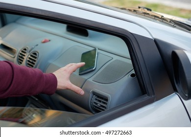 Hand of a thief stealing a mobile phone from a parked car