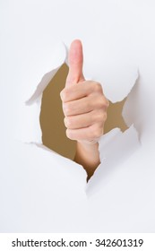 Hand through the hole in paper with woman thumb up
