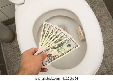 Hand throwing 100 dollar bills in toilet