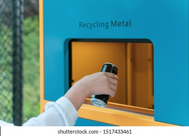 hand throwing aluminum can into recycle box and get categorized in modern street.