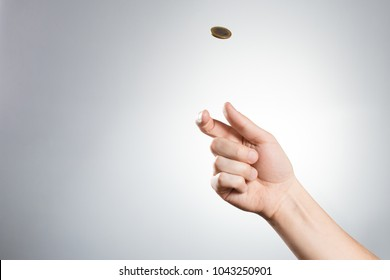 Hand throwing up a coin on white background