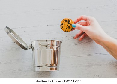 hand throwing cookie into a trash can, metaphor about website cookies and user tracking technologies