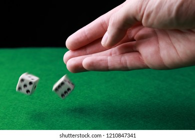 Hand throwing a couple of dice.  (Dice in motion)