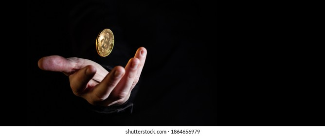 Hand throwing golden bitcoin in the air on black background - narrow banner with copy space