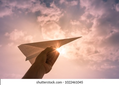Hand throwing paper airplane. Flying high in the sky. Freedom, travel concept.