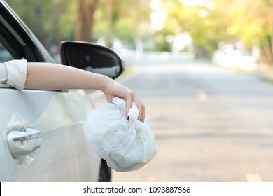 Hand throwing plastic bag on the road