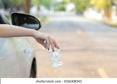 Hand throwing plastic bottle on the road