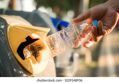 Hand throwing plastic bottle in recycling bin, global warming