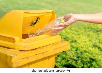 Hand throwing plastic water bottle in recycle bin