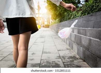 Woman's hand throwing trash on the floor in public areas, people disposed improperly throwing away garbage the way while walking,environmental conservation,plastic pollution,stop using plastic bags