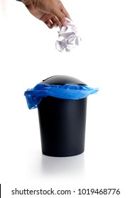 Hand throwing trash to rubbish bin over white background