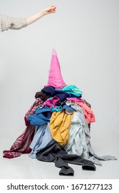 hand throws clothes into a pile with used clothes. Pile of used clothes on a light background. Second hand for recycling