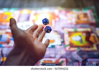 Hand throws the dice on the background of colorful blurred fantasy Board games, gaming moments in dynamics