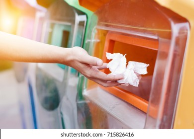 Hand throws tissues into general trash bin,Concept for environmental protection and Help reduce global warming.This is a valid garbage dump.