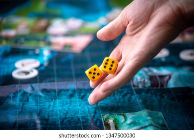 Hand throws two yellow dice on the blue playing field. Gaming moments in dynamics. Luck and excitement. Board games strategy