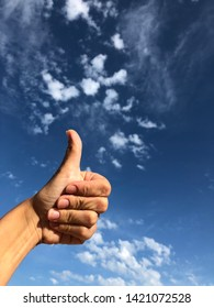 hand with thumb up against the sky with small clouds