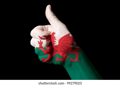 Hand with thumb up gesture in colored wales national flag as symbol of excellence, achievement, good, - useful for tourism and touristic advertising